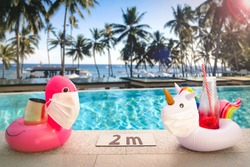 Inflatable pool toys at tropical resort pool wearing face masks staying 2 meters aside to keep social distance during COVID-19 pandemic. Concept of travel industry difficulties during summer 2020.