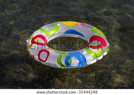 Inflatable ring floating on the sea, transparent clear water