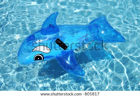 Inflatable toy dolphin on blue swimming pool on spanish vacation urbanisation