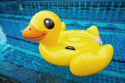 Inflatable yellow ducks in swimming pool.Concept for summer fun party.