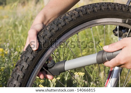Inflating the tire of a bicycle in the grass meadow
