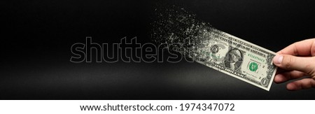 Inflation, dollar hyperinflation. Banner with black background. One dollar bill is sprayed in the hand of a man on a black background. The concept of decreasing purchasing power, inflation.