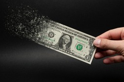 Inflation, dollar hyperinflation with black background. One dollar bill is sprayed in the hand of a man on a black background. The concept of decreasing purchasing power, inflation.
