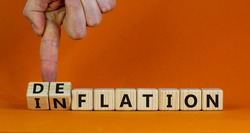 Inflation or deflation symbol. Businessman turns cubes and changes the word inflation to deflation. Beautiful orange background, copy space. Business, inflation or deflation concept.