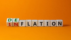 Inflation or deflation symbol. Turned cubes and changed the word inflation to deflation. Beautiful orange background, copy space. Business, inflation or deflation concept.