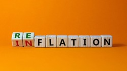 Inflation or reflation symbol. Turned cubes and changed the word inflation to reflation. Beautiful orange background, copy space. Business, inflation or reflation concept.
