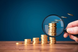 Inflation, tax, cash flow and another financial concept. Financial advisor focused on decreasing value of money in post-covid era. Hand with magnifying glass focused on coins fly away.