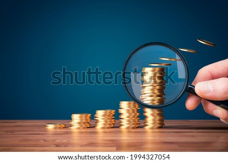 Inflation, tax, cash flow and another financial concept. Financial advisor focused on decreasing value of money in post-covid era. Hand with magnifying glass focused on coins fly away. Photo stock ©