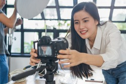 Influencer and content creator in digital marketing concepts. Young woman adjusting her digital camera prepare for record video content to her channel.
