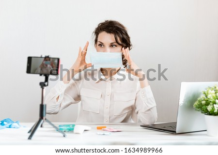 Influencer Girl blogger in medical mask talks about coronavirus. Woman recording video blog tells how to protect yourself from 2019-nCov. Bloger talks mers-cov how to use of alcohol wipes, thermometer