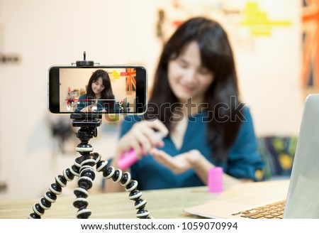 influencer marketing,Live video blogger concept.young vlogger girl live broadcasting  about cosmetic content via mobile phone