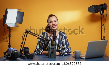 Influencer talking about professional video equipment in her studio set. Professional videography gear review by content creator new media star influencer on social media. Foto stock ©