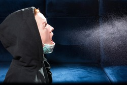 Influenza, cold, coronavirus. Infection through an airborne droplet. Girl in a hood and in a medical mask in front of a cloud of drops in the air