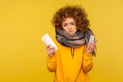 Influenza treatment. Upset depressed flu-sick woman with curly hair, wrapped in warm scarf, holding napkin and pills, frowning with displeased miserable expression. studio shot, yellow background