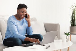 Informal Call. Emotional young curvy african american woman talking on her smartphone, sitting on the couch, using laptop, typing on computer keyboard. Copy space. Communication Concept.
