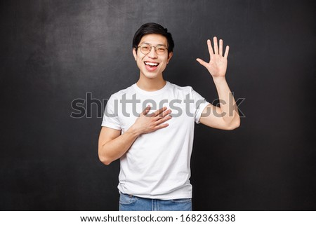 Informal greeting concept. Outgoing attractive young asian guy introduce himself in front of team, raise hand and pointing at him as saying own name, smiling hello gesture, black background