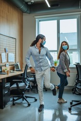 Informal greeting foot bump by business people in the office during outbreak of the global pandemic COVID-19. Avoiding handshakes in a new normal.