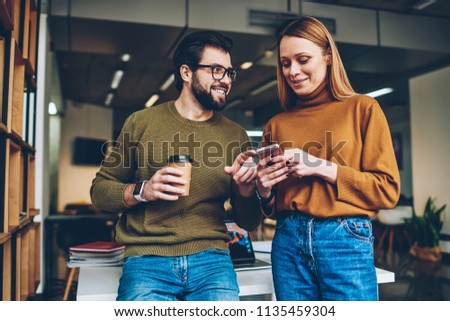 Informal meeting of two young hipster teenagers blogging via modern smartphone connected to wifi indoors, attractive happy girl dialing number while bearded man staying near and enjoying coffee