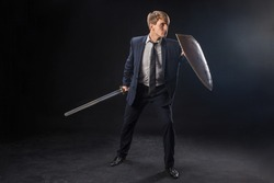 Information and privacy protection. The concept of security versus personal information protection. A man in a suit with a shield and a sword