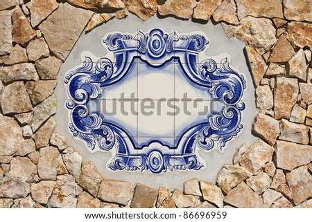 Information panel of traditional Portuguese tiles hand-painted blue and white, placed in a rustic stone wall Orange