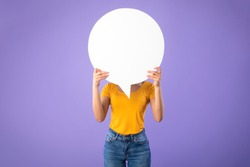 Information, Thought, Quote And Opinion Concept. Young woman hiding her face behind blank white speech bubble, isolated on purple studio background. Empty space for text or feedback on balloon circle