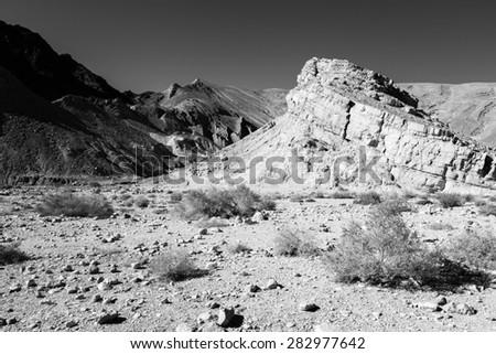 Infrared black and white, B&W, stone desert mountain cliff crag, Negev desert, Israel.