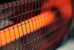 Infrared heater. Cozy warmth for home. The included electric red heater close-up with a metal grill is an excellent solution in winter for heating a room.
