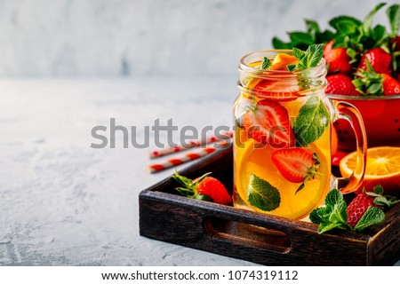 Infused detox water with orange, strawberry and mint. Ice cold summer cocktail or lemonade in glass mason jar