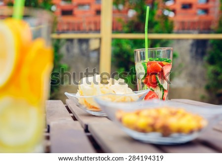 Infused fruit water cocktails and snacks bowls over a wooden table outdoors. Healthy organic summer drinks concept.
