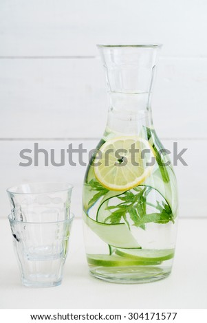 Infused water with cucumber, lemons and mint in a pitcher