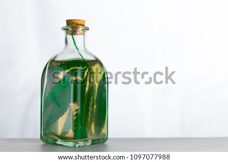 Infusion on the leaves of marijuana in a jar on a white background.