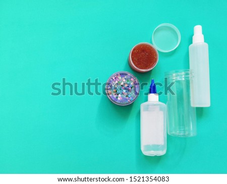 Ingredients, bottles, jars for making a popular children's toy from glue. Homemade trendy slime for entertainment and hobbies. On a bright turquoise blue background with empty place for text. #1521354083