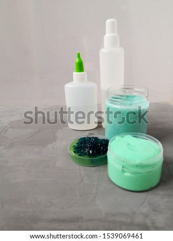 Ingredients, bottles, jars for making a popular children's toy from glue. Homemade trendy slime for entertainment and hobbies.  #1539069461