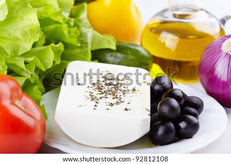 Ingredients for a Greek salad - vegetables, olive oil and feta cheese