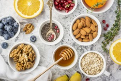 Ingredients for a healthy breakfast, nuts, oatmeal, honey, berries, fruits, blueberry, orange, pomegranate seeds, almonds, walnuts. The concept of natural organic food in season. Top view
