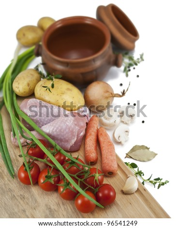 Ingredients for a roast chicken in a pot : chicken, potatoes, carrots, tomatoes, onions, mushrooms, garlic, black pepper and bay leaf. Isolated on white .