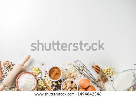 Ingredients for autumn winter festive baking - flour, brown sugar, eggs, chocolate drops, butter, cinnamon on white stone or concrete background.Top view copy space.