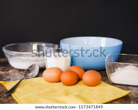Ingredients for baking dough. flour, eggs, milk. Baking ingredients. Spoon on a marble table. Preparation for cooking.