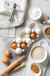 Ingredients for baking on a culinary background. Eggs, flour, cinnamon, sugar, soda on the kitchen table. Concept of preparation for baking. Top view with space for text