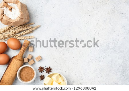 Ingredients for baking on background. Eggs, wheat flour, cubed butter, star anise, brown sugar cubes and rolling pin on concrete background with copy space #1296808042