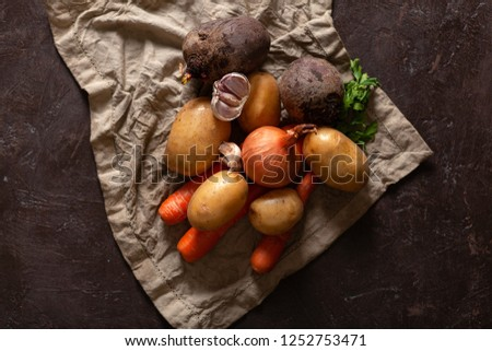 Ingredients for beet soup. Carrots, beets, onions, potatoes, greens on a dark textured background. Set of vegetables for soup. Top view with space, cooking concept