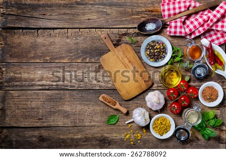 Ingredients for cooking and empty cutting board on an old wooden table. Food background  with copyspace