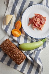 ingredients for cooking bruskets with grain bread ham, courgette, cherry tomatoes, cheese on tablecloths in a blue strip. High quality photo