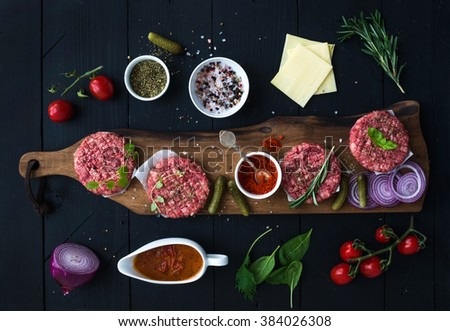 Ingredients for cooking burgers. Raw ground beef meat cutlets on wooden chopping board, red onion, cherry tomatoes, greens, pickles, tomato sauce, cheese, herbs and spices over black background