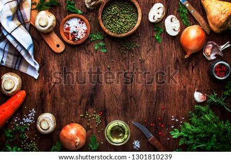 Ingredients for cooking green lentils with mushrooms and vegetables, spices and herbs, vintage wooden kitchen table background, place for text. Vegan or vegetarian food, clean food concept.