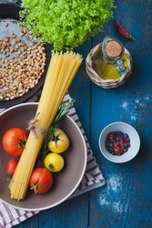 Ingredients for cooking italian pasta - olive oil, tomatoes, pine nuts, spice and herbs on old wooden table, mediterranean cuisine recipe