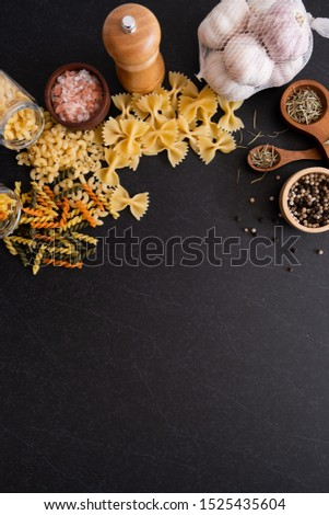 Ingredients for cooking Italian pasta - spaghetti, tomatoes, basil, oil and garlic. Italian food. Top view with space for text. Fettuccine with ingredients for cooking on black stone slate. - Image
