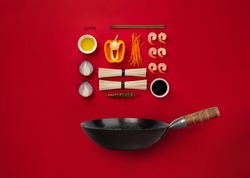 Ingredients for cooking noodles in wok pan: noodles, shrimps, onion, cut carrot, bell pepper, chili, soy sauce, oil on red background. Top view, flat lay minimal design, Asian cuisine concept