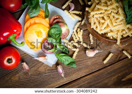 Ingredients for cooking pasta - fusilli, tomatoes, peppers, garlic and basil