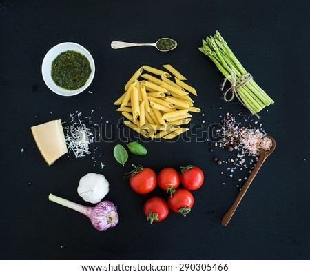 Ingredients for cooking pasta. Penne, green asparagus, basil, pesto sauce, garlic, spices, parmesan cheese and  cherry-tomatoes on dark grunge backdrop, top view